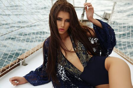 fashion outdoor photo of gorgeous woman with dark hair in elegant swimsuit posing on yacht