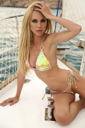 girls in bikini: fashion outdoor photo of gorgeous sexy woman with blond hair in elegant swimsuit posing on yacht