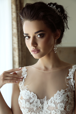 fashion interior photo of gorgeous bride in luxurious wedding dress posing in bedroom