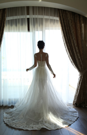 fashion interior photo of gorgeous bride in luxurious wedding dress posing at bedroom 免版税图像