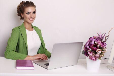 businesslike: fashion studio photo of beautiful businesslike woman in elegant outfit working on computer in office