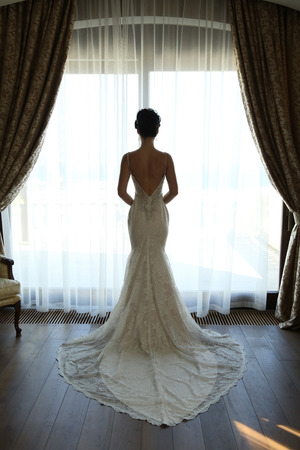 luxurious interior: fashion interior photo of gorgeous bride in luxurious wedding dress posing at bedroom Stock Photo