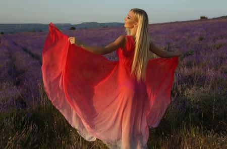 塑造华美的肉欲的妇女室外照片有金发的在摆在开花淡紫色领域的典雅的成套装备