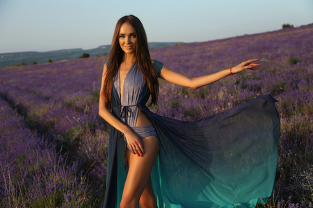 woman in field: fashion outdoor photo of gorgeous sensual woman with dark long hair in elegant outfit posing at blossom lavender field