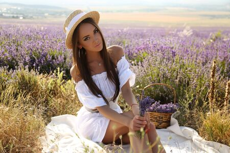 woman hairstyle: fashion outdoor photo of gorgeous sensual woman with dark long hair in elegant outfit posing at blossom lavender field