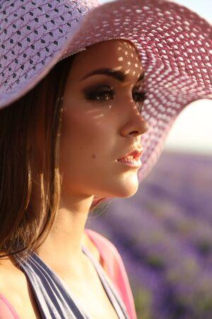 mujer elegante: foto al aire libre de la manera de la mujer sensual hermosa con el pelo largo y oscuro en traje elegante que presenta en el campo de lavanda en flor