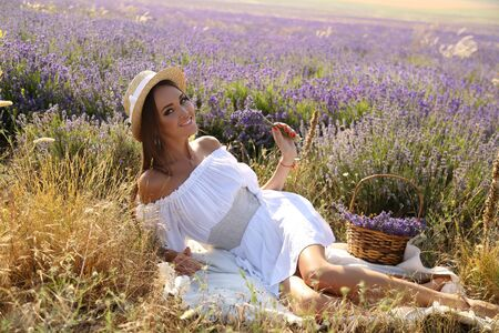 moda foto all'aperto di splendida donna sensuale con i capelli lunghi scuri in abito elegante che presentano al campo di lavanda fiore