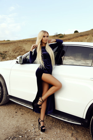 fashion photo of gorgeous sexy woman with blond hair in elegant dress posing in luxurious auto Stock Photo