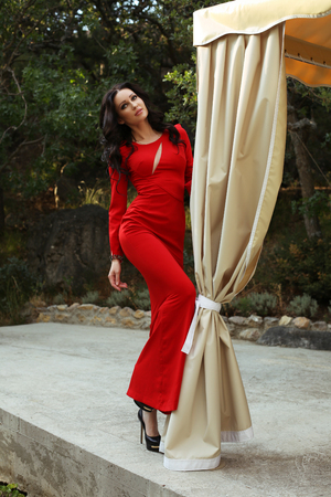 red dress: fashion outdoor photo of beautiful woman with dark hair in elegant red dress, posing at summer garden