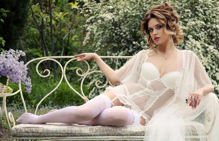 pantimedias: foto al aire libre de la moda de la mujer magnífica con el pelo oscuro en ropa interior elegante, descansando en la cama, situada en el jardín de flor de verano Foto de archivo