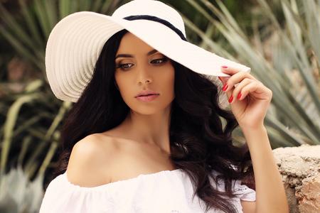 Mode Outdoor-Foto von wunderschönen Frau mit dunklen Haaren in einem eleganten weißen Kleid und Hut