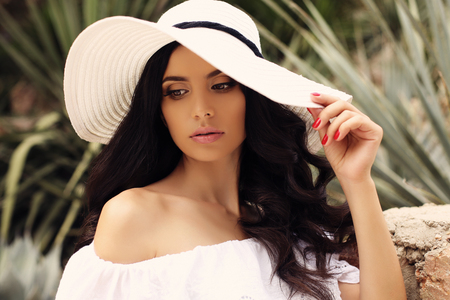 foto al aire libre de la moda de la mujer magnífica con el pelo oscuro en elegante vestido blanco y un sombrero