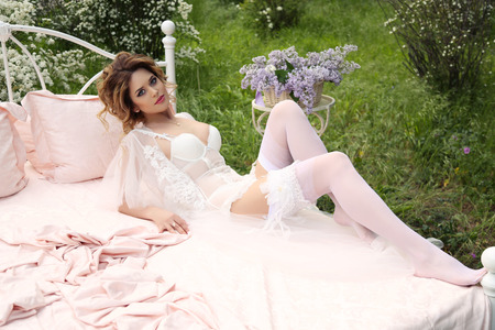 the girl in stockings: fashion outdoor photo of gorgeous woman with dark hair in elegant lingerie, relaxing in bed, situated at summer blossom garden Stock Photo