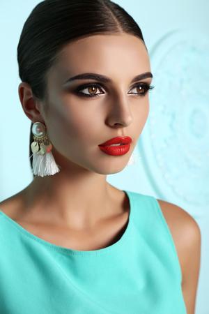 Mode Outdoor-Foto der schönen jungen Frau mit dunklen Haaren und hellen Make-up