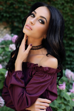 fashion outdoor photo of gorgeous woman with dark hair in elegant dress posing in summer garden Stock Photo