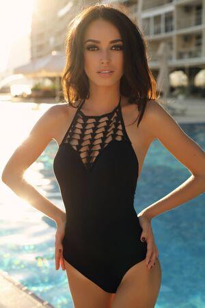 maillot de bain fille: mode photo en plein air de femme magnifique avec des cheveux noirs en maillot de bain élégant posant à côté de la piscine
