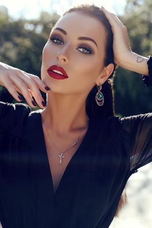 foto al aire libre de la moda de la mujer magnífica con el pelo oscuro en el elegante vestido posando en el jardín de verano