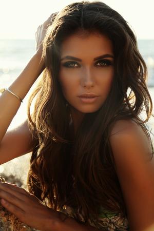 fashion outdoor photo of gorgeous sexy woman with dark hair in elegant dress posing on summer beach Foto de archivo