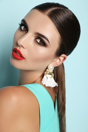 fashion outdoor photo of beautiful young woman with dark hair and bright makeup