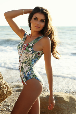fashion outdoor photo of gorgeous sexy woman with dark hair in elegant swimsuit posing on summer beach