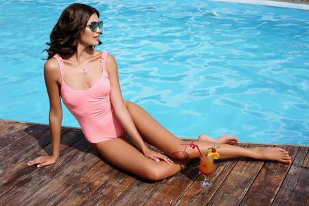 fashion outdoor photo of gorgeous sexy woman with dark hair in elegant swimsuit posing beside swimming pool with cocktail