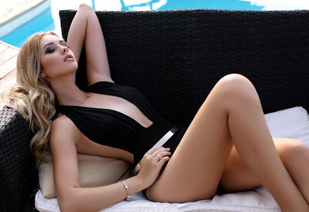 mujer elegante: foto al aire libre de la manera de la mujer atractiva hermosa con el pelo rubio en traje de baño elegante que presenta al lado de la piscina