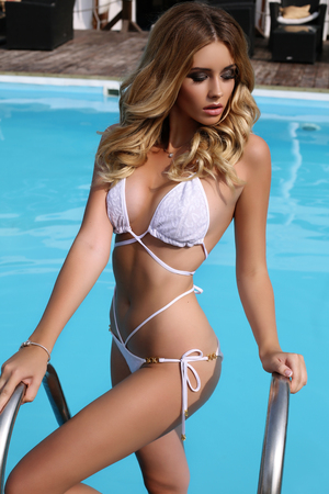 cabello rubio: foto al aire libre de la manera de la mujer atractiva hermosa con el pelo rubio en traje de baño elegante que presenta al lado de la piscina