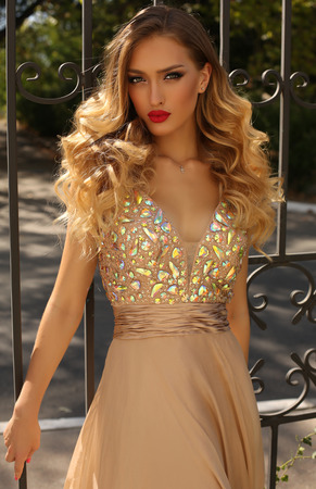 sequins: fashion photo of gorgeous young woman with blond curly hair and bright makeup, in luxurious sequin dress posing outdoor Stock Photo