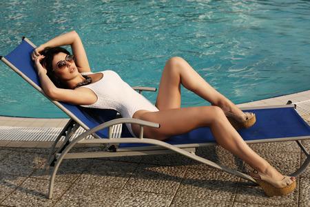 mujer elegante: foto al aire libre de la manera de la mujer atractiva hermosa con el pelo oscuro en traje de baño elegante que presenta al lado de la piscina