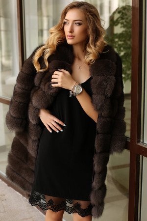 luxurious: fashion outdoor photo of gorgeous sensual woman with blond hair in luxurious fur coat walking by autumn city