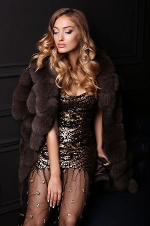 divan: fashion studio photo of gorgeous sensual woman with blond hair in luxurious dress and fur coat