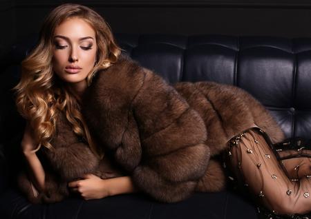 fashion studio foto van mooie sensuele vrouw met blond haar in een luxe jurk en bontjas