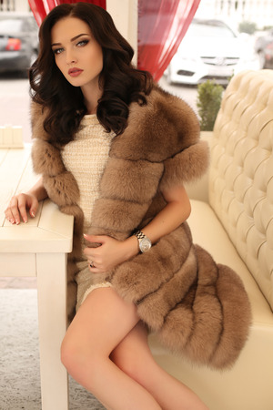 luxurious: fashion outdoor photo of gorgeous sensual woman with dark hair in elegant clothes and luxurious fur coat, sitting in cafe