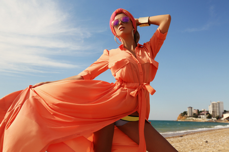 fashion outdoor photo of gorgeous sexy woman in luxurious outfit, posing on summer beach
