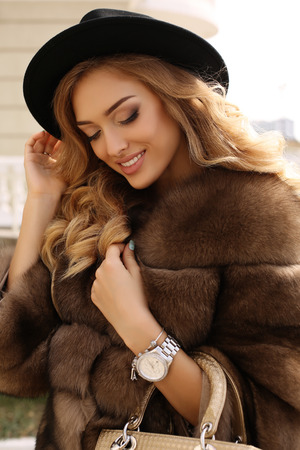fashion outdoor photo of gorgeous sensual woman with blond hair in luxurious fur coat and hat, walking by autumn city