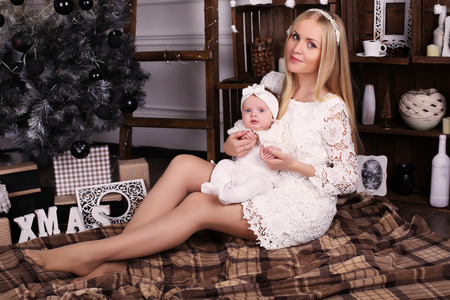 navidad elegante: tender photo of beautiful mother with luxurious blond hair posing with her cute little baby girl beside Christmas tree in cozy home