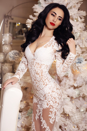 female christmas: fashion interior photo of beautiful sensual woman with long dark hair wears elegant dress posing  beside decorated Christmas tree