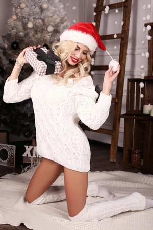 charming girl: fashion studio photo of beautiful girl with blond hair and charming smile,posing beside Christmas tree and presents