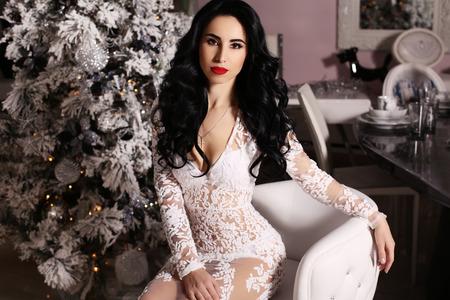 sensual woman: fashion interior photo of beautiful sensual woman with long dark hair wears elegant dress posing  beside decorated Christmas tree