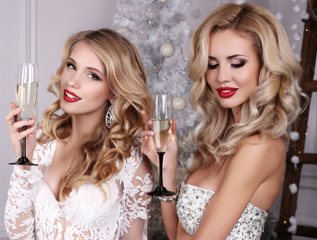 fashion studio photo of beautiful girls with blond hair and charming smiles,posing beside Christmas tree and presents with glass of champagne Stock Photo