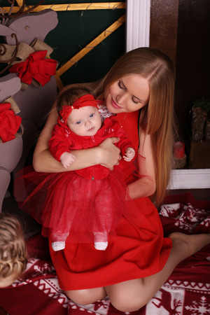 cabello rubio: tender photo of beautiful mother with luxurious blond hair posing with her cute little baby girl beside Christmas tree in cozy home