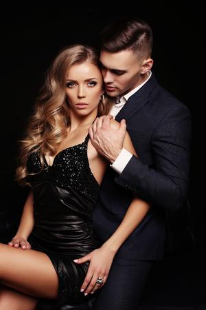 photo de studio de mode de beau couple sexy. superbe femme aux cheveux blonds et bel homme en habits élégants