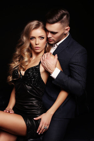 fashion studio photo of sexy beautiful couple. gorgeous woman with blond hair and handsome man in elegant clothes