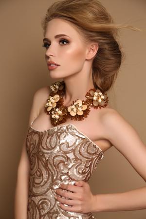 mujeres elegantes: foto de estudio de moda de mujer sensual hermosa con el pelo rubio y el maquillaje brillante con el collar lujoso y elegante vestido