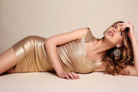 woman dress: fashion studio photo of gorgeous sensual woman with blond curly hair  in elegant gold dress Stock Photo