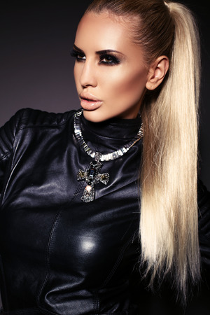 fashion studio photo of gorgeous sensual woman with blond hair and bright makeup, in leather jacket and necklace