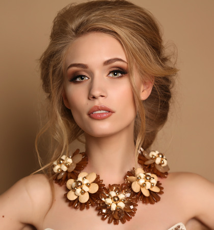 woman hairstyle: fashion studio photo of gorgeous sensual woman with blond hair and bright makeup with luxurious necklace and elegant dress Stock Photo