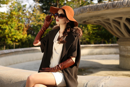 fashion outdoor photo of gorgeous sensual woman with dark hair in elegant luxurious coat, wool hat and leather gloves, walking by autumn city Standard-Bild