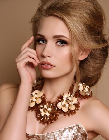 foto de estudio de moda de mujer sensual hermosa con el pelo rubio y el maquillaje brillante con el collar lujoso y elegante vestido