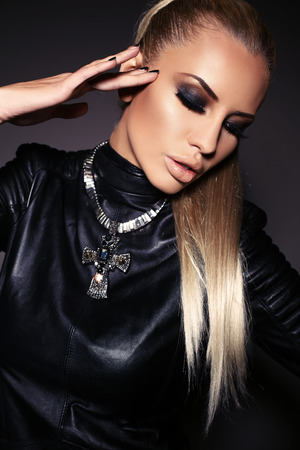 fashion studio photo of gorgeous sensual woman with blond hair and bright makeup, in leather jacket and necklace Stockfoto